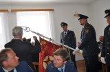 starosta obce připíná pamětní stuhu k slavnostnímu praporu